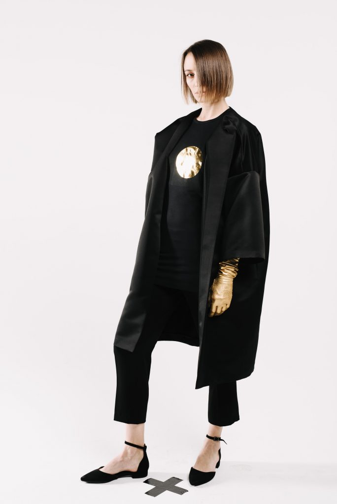 """Jasno je i ovom """"Spring 2019"""" Collection, da Dragana Ognjenović neće odustati od svog paralelnog monohromatskog i minimalističkog modnog univerzuma. Iznova, vidljiva je Draganina """"opsesija"""" harmonijom i jednostavnošću a čista silueta oblikovana je u katkad strog, solidan odevni komad - sako, sa spektrom namena od posebnih, poslovnih i svakodnevnih prilika. Haljine u kolekciji Dragana Ognjenović Spring 2019 su strastveni kontrast klasičnim sakoima. Načijene od mekih a postojanih žoržet tkanina u svežini pastelnih bež nijansi sa neizbežnom crnom, haljine čine ovu kolekciju """"intelektualno zavodjivom"""". Autorski pečat daju specijalno izrađeni grafčki detalji aplicirani na koži i tkaninama vidljivi na haljinama, suknjama i tašnama pojačavajući utisak unikatnog. I ovom kolekcijom Dragana govori o verdnostima i beskompromisnim životnim stilovima kao i o poimanju """"luksuza"""" koji demonstrira u svedenoj bezvremenskoj lepoti D.O. modnog sveta, trudu i detaljima izrade."""